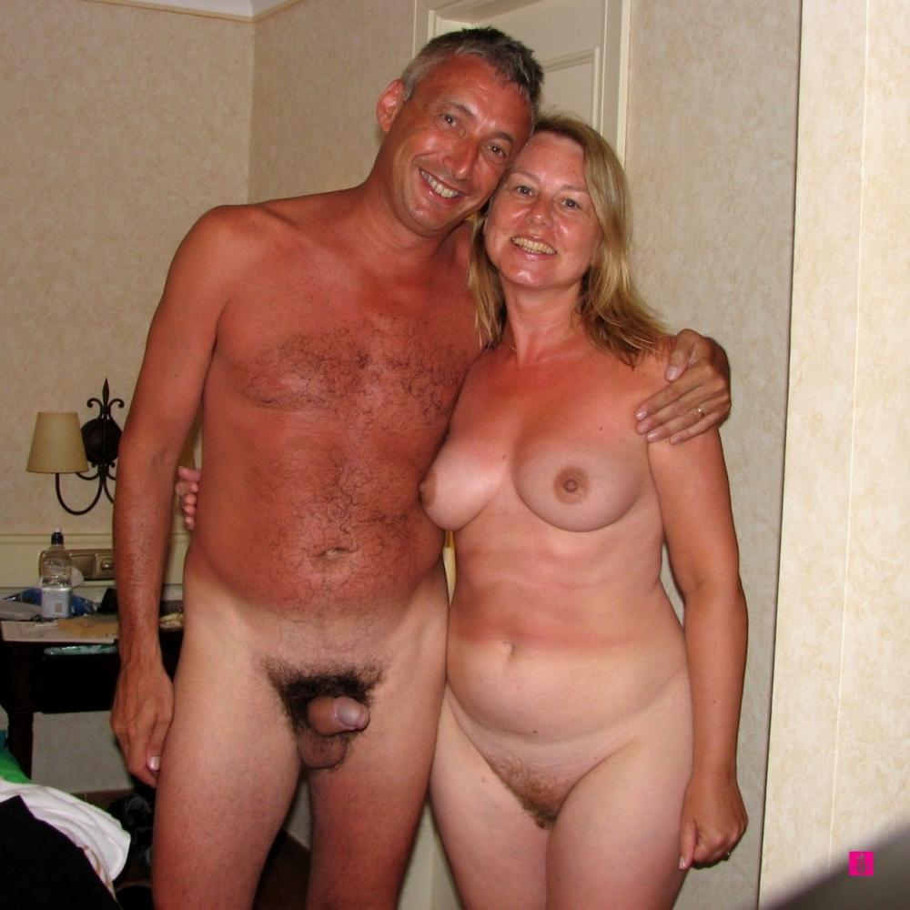 happy naked couple on a beach with guy's pierced semi-hard hairy
