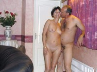 Nudist photo showing guy with small trimmed dick kissing some older woman with flabby breasts and shaved vagina